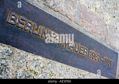 plate that signifies the course of the berlin wall embedded in the sidewalk - Stock Photo