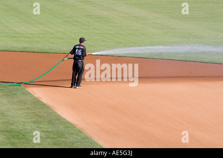 Worker watering infield dirt of a baseball diamond in preparation for a baseball game - Stock Photo