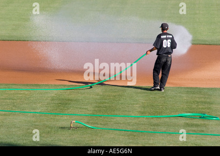Worker watering down infield dirt of baseball diamond before game creating a wall of water moving the hose back - Stock Photo
