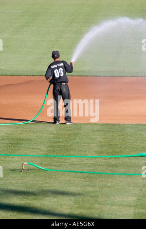 Worker watering infield dirt of baseball diamond before a baseball game - Stock Photo