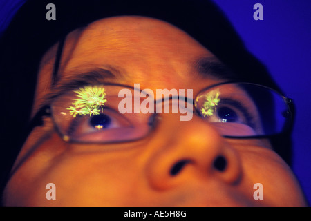 Man looking up at fireworks exploding in the night which are reflecting in his eyeglasses - Stock Photo