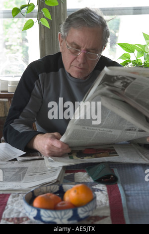 Senior man in his 70s reading the New York Times newspaper at the breakfast table - Stock Photo