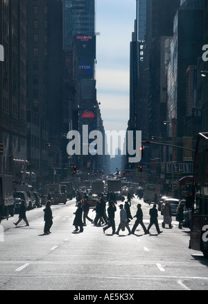 Looking down Seventh Avenue in New York City with tall buildings and red lights stopping traffic allowing pedestrians - Stock Photo