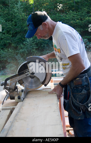 Carpenter in his mid 50s lowering the arm of compound miter saw to cut a piece of lumber at a construction site - Stock Photo