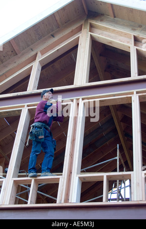 Carpenter standing on second story framed window sill at residential construction site - Stock Photo
