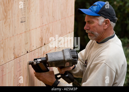 Carpenter using nail gun to secure plywood to exterior of house to build shear wall on a home construction site - Stock Photo