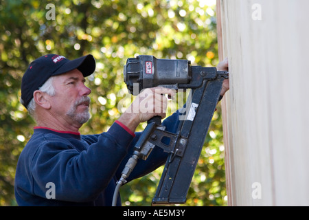 Carpenter using nail gun to secure plywood to exterior of house to build shear wall on a residential home construction - Stock Photo