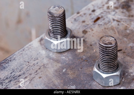 Two galvanized steel bolts secured to rusty metal plate with nuts - Stock Photo