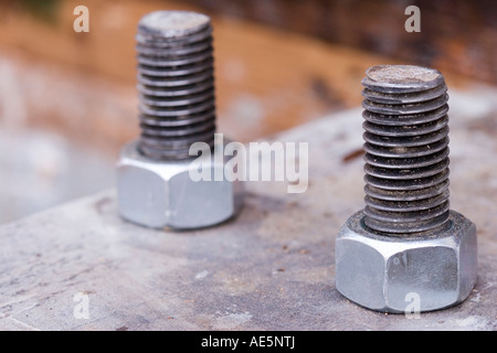 Two galvanized steel bolts with nuts secured to rusty metal plate - Stock Photo
