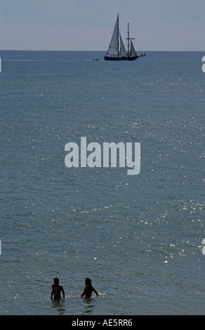 Bathers in the sea off Abufeira Algarve Portugal Yacht skirting the horizon - Stock Photo
