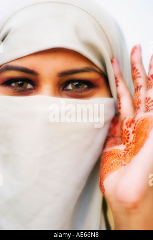 Beautiful woman wears hijab, with hina or hennah painted on palm of hand - Stock Photo