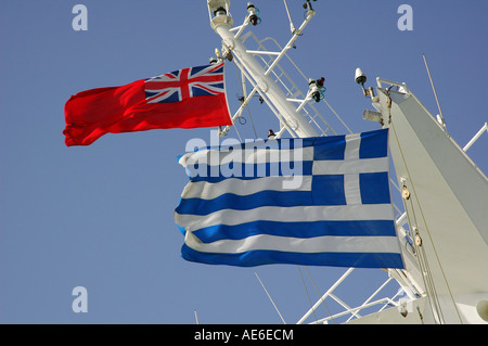 British merchant Red Ensign flag and Greek flags flying side by side on a cruise ship - Stock Photo