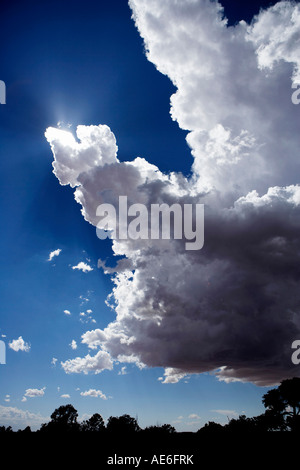 The edge of a thunderstorm in Utah.  Puffy white clouds edge out to a blue sky with bright rays of sunlight. - Stock Photo