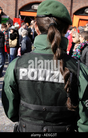 female Police officer watching  the Fasching in Munich at Viktualienmarkt, Bavaria, Germany. Photo by Willy Matheisl - Stock Photo