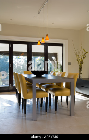 modern table and chairs in dining room designed by Smiros Architects - Stock Photo