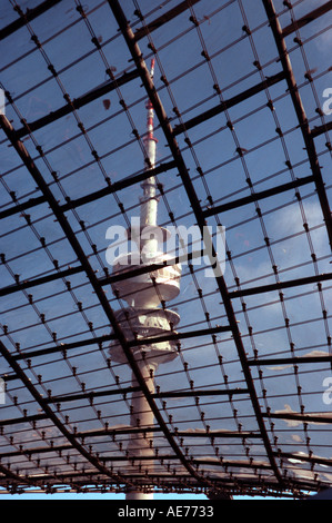 Telecommunications tower at the Olympic Park in Munich Germany seen through the roof of the Olympic hall with snow - Stock Photo