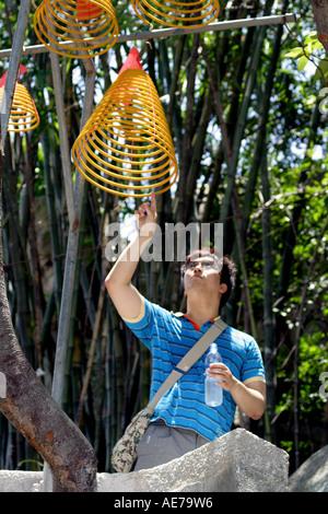 Korean Tourist Touching Coiled Incense Sticks at the A-Ma Temple or Tin Hau Temple, Macau, SAR, China - Stock Photo