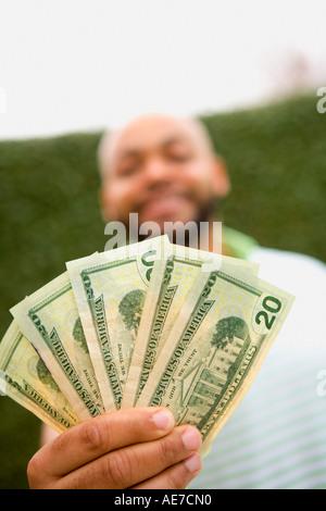 Man holding twenty dollar bills - Stock Photo