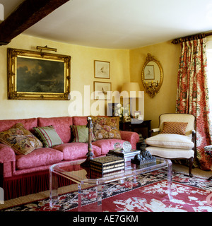 Sofa and armchair on patterned rug in traditionally British sitting room interior - Stock Photo