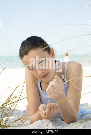 Preteen girl lying on stomach on beach, contemplatively