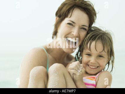 Mother holding daughter at the beach, close-up - Stock Photo