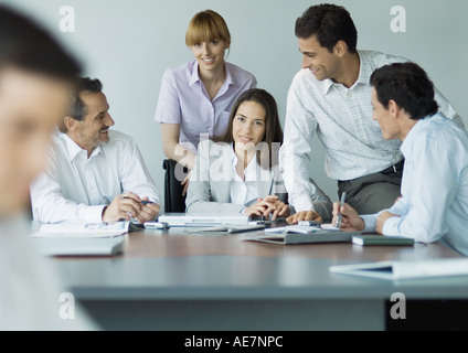 Business colleagues gathered around table, smiling - Stock Photo