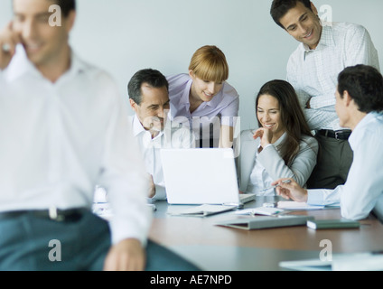 Business colleagues gathered around laptop, smiling - Stock Photo