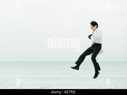 Businessman on beach, using cell phone and jumping - Stock Photo