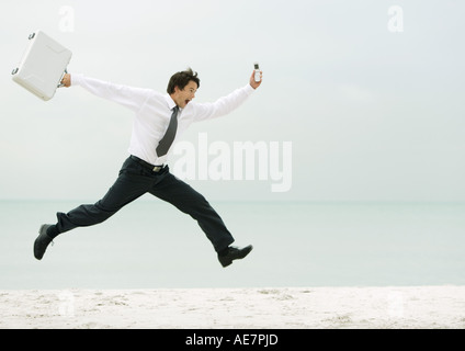 Businessman running and jumping on beach - Stock Photo