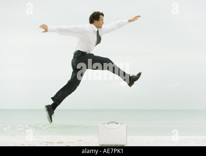 Businessman on beach, jumping over briefcase - Stock Photo