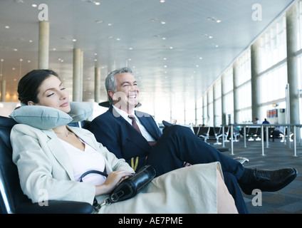 Business travelers sitting in airport lounge, woman napping with neck pillow next to smiling man - Stock Photo