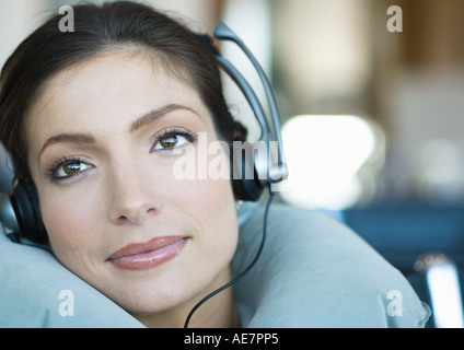 Woman wearing headphones and using neck pillow - Stock Photo