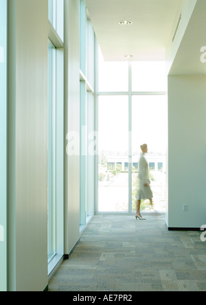 Silhouette of businesswoman walking by at end of corridor - Stock Photo