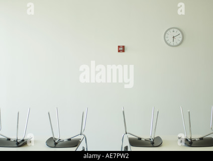 Chairs upside down on tables and clock on wall - Stock Photo