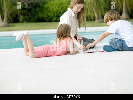 Three kids playing boardgame by edge of pool - Stock Photo