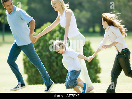 Family holding hands and running - Stock Photo