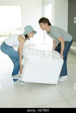 Couple moving armchair together - Stock Photo