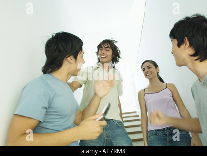 Four young friends meeting in stairway - Stock Photo