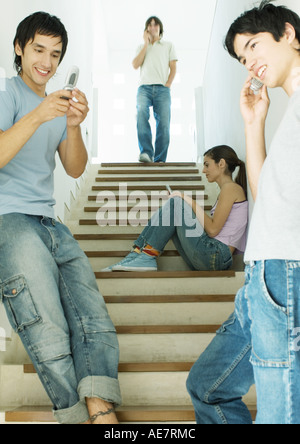 Four young adults, each using cell phone in stairway - Stock Photo