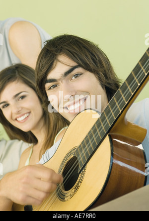 Young man playing guitar for friends - Stock Photo