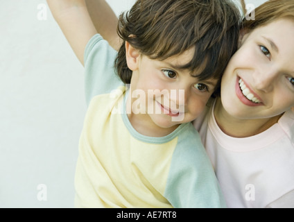 Brother and sister having fun, arms raised, close-up - Stock Photo