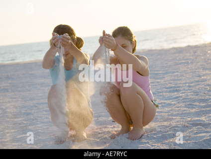 Two girls letting sand run through hands on beach - Stock Photo