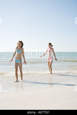 Two girls walking on beach, one with mouth open in surprise - Stock Photo