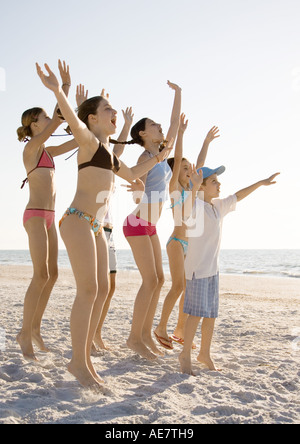 Group of kids jumping and waving on beach - Stock Photo