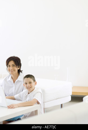 Boy and mature woman using laptop