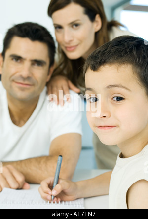 Boy doing homework with parents in background - Stock Photo