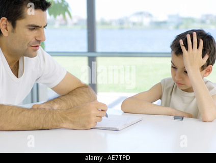 Boy doing homework with father's help, cropped - Stock Photo