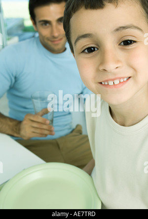 Boy and father with dishes - Stock Photo