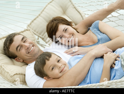 Family lying in hammock, smiling - Stock Photo