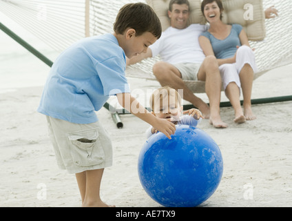 Boy and baby playing with ball while parents watch from hammock - Stock Photo